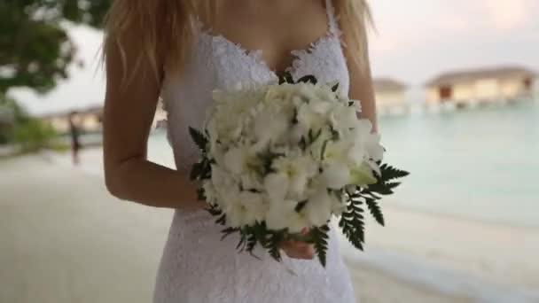 First look of young wedding couple. Bride goes to wedding ceremony on romantic tropical island on the white sand beach near azure lagoon ocean