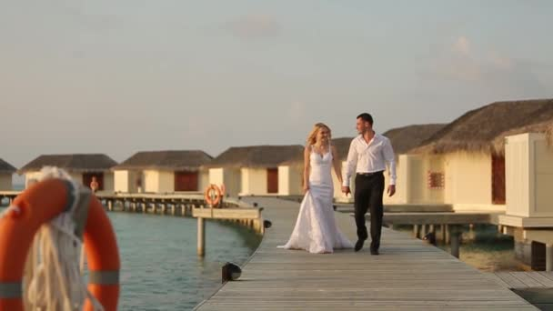 Camera follows bride and groom as they walk to ceremony along shore line near bungalows on bridge at luxury resort on Maldives island. Newlyweds enjoying honeymoon. Exotical tropical wedding concept.