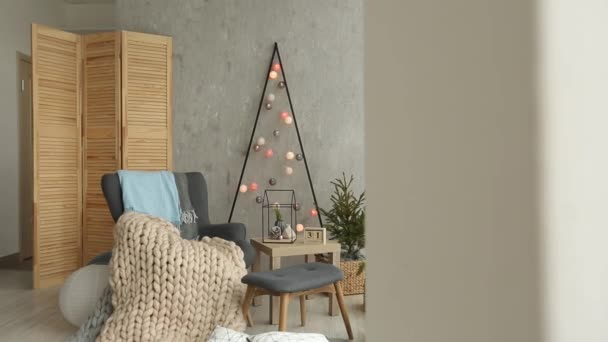 Stylish christmas scandinavian interior with an elegant armchair and warm merinos plaid. Comfort home with nordic new year decor. Minimalistic christmas tree with garlands and lights in light room.