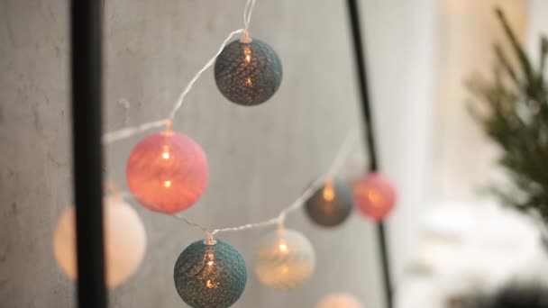 Stylish christmas scandinavian interior details. Comfort home with nordic new year decor. Eco friendly minimalistic christmas tree with garlands, decoration and lights in light room.