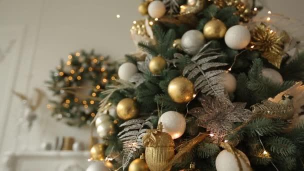 Elegáns fehér belső és fenyők Karácsonyi koszorú tele arany díszek, a játékok, a fények és a koszorúkat. Koszorú a háttérben. Új évvel ezelőtt előest otthon.