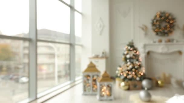 Interni eleganti di natale bianco con abeti decorati, camino, lanterne, lampade, candele, ghirlanda, urti e regali. Comfort di casa con lalbero di Natale pieno di decorazioni in oro, luci e