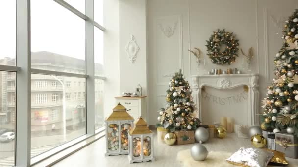 Stylish white christmas interior with decorated fir trees, fireplace, lanterns, lamps, candles, wreath, bumps and gifts. Comfort home with christmas tree ...