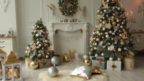 Stylový bílý vánoční interiér s zdobené jedle, krb, lucerny, lampy, svíčky, věnec, hrboly a dary. Pohodlí s vánoční stromeček plný zlaté ozdoby, světla domů a