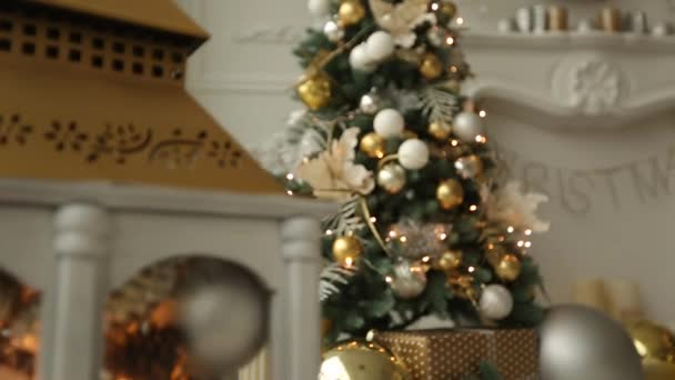 Stylish white christmas interior with decorated fir trees, fireplace, lanterns, lamps, candles, wreath, bumps and gifts. Comfort home with christmas tree full of golden decorations, lights and
