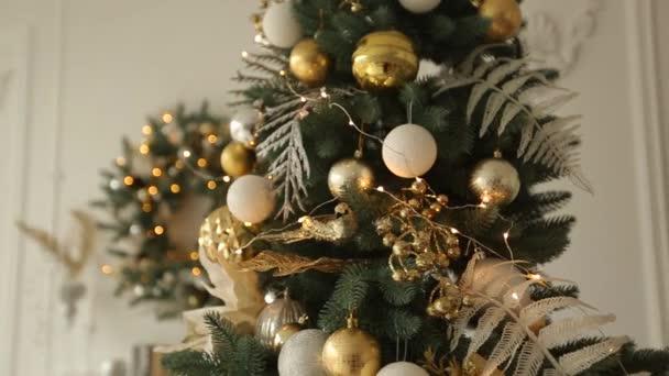 Stylový bílý vánoční interiér s zdobené jedle. Pohodlí domů s vánoční stromeček plný zlaté ozdoby, věnce a girlandy na pozadí světla. New Years Eve.