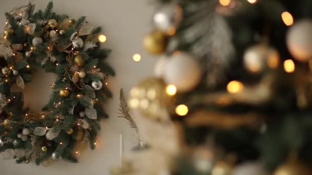 Stylish white interior with fir christmas trees, and wreath full of golden decorations, toys, lights and garlands. Wreath on background. New Years Eve at home.