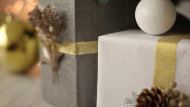 Stylový bílý interiér s handmade dary a dárky zdobené stuhami a boule pod vánoční stromeček. Komfortní teplo domov plný zlaté ozdoby, světel a girlandy na Silvestra.