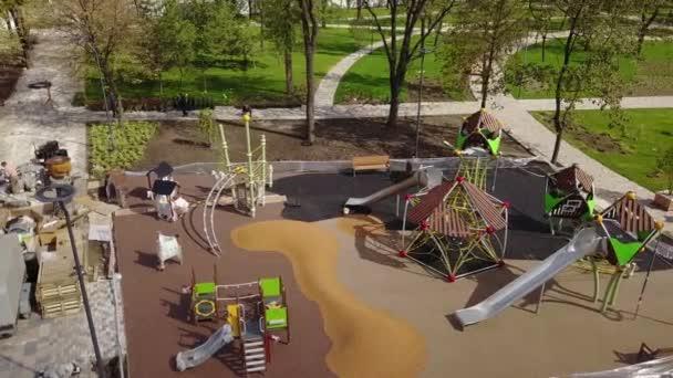 Letecké záběry z luxusní dětského hřiště v parku na předměstí. Rekonstrukce parku pro děti. Dělníci, kterým barevné pryžovou drobeček na zemi. Staveniště