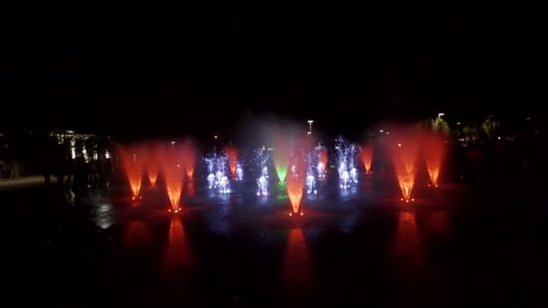 Colorful dancing fountain at night. Slow-motion footage of jets of water on a dark background. Unrecognizable people silhouettes.