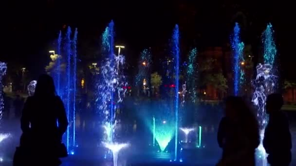 Colorful dancing fountain at night. Slow-motion closeup footage of jets of water on a dark background. Unrecognizable people silhouettes.
