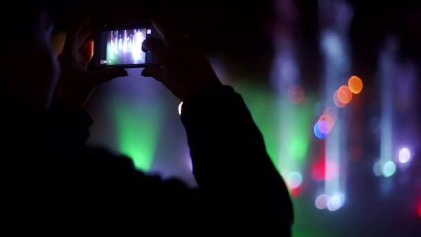 Colorful dancing fountain at night. Slow-motion closeup footage of jets of water on a dark background. Unrecognizable man silhouette filming on smartphone.
