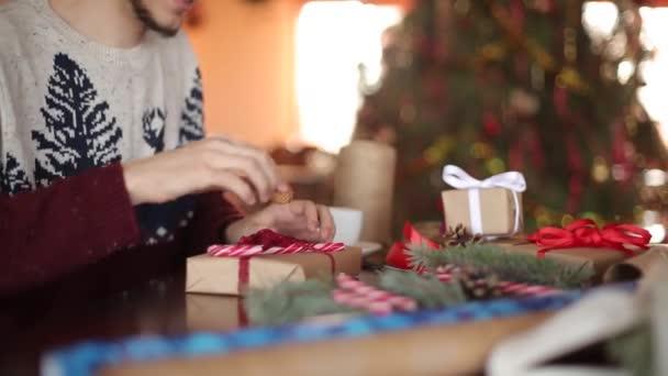 Zavřít pohled na mans ruce vázání mašlí na dárky k Vánocům. Muž obtékání současné krabic v dokumentu přidáním jedle větve, šišky, třtiny bonbony na dřevěný stůl doma u nový rok strom.