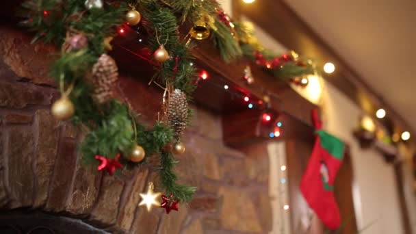 Warm cozy stone fireplace decorated for Christmas with wreath, stockings, garland lights. Mantelpiece with decorations for New Year holidays. Authentic festive interior decor. Dolly shot.