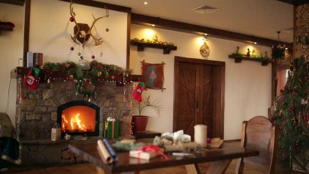 Hořet oheň v krbu zdobený věnec světel, věnec, Punčochy a dary na Štědrý den. Dárky a obalový materiál: balicí papír, větve stromů jedle, kužely a stuhy na stole