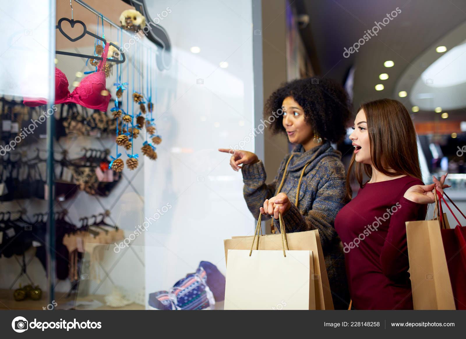 36a53521a0 Dos mujer mestiza joven multiétnica feliz de las compras de ropa interior  junto a la ventana de la tienda de ropa boutique