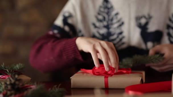 Töve mans kezében árukapcsolás egy íj, egy karácsonyi ajándékok közelében kandalló, csomagoló ládák, mázolás, a fenyő ágak, tobozok, nád cukorka a táblázatot, majd kínál mutatja be, a kamera.