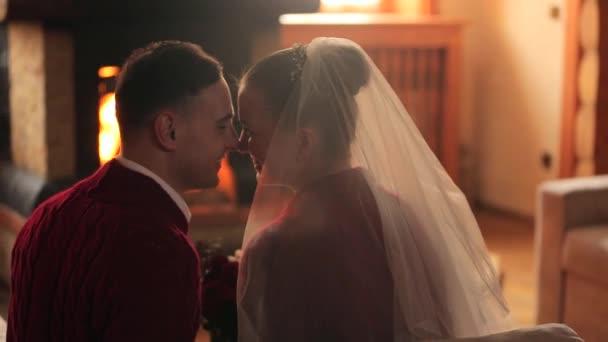 Svatební pár v lásce zahříval v červené svetry u krbu. Nevěsta a ženich relaxovat a líbat teplého krbu a oteplování se v dřevěné chatě protokolu. Zimní svátky vánoční a svatební koncept.
