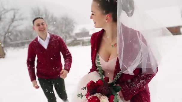 Mladí svatební pár běh, Bavíte se drží za ruce v ski resort village s dřevěnými chalupami blízko protokolů. Zimní svatební inspirace. Ženich a nevěsta na líbánky. Novomanželé na dovolené.