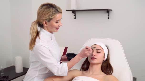 Kosmetologie-Spezialist mit Gesichtsmaske mit Pinsel, macht die Haut hydratisiert und gesund. Attraktive Frau entspannend mit geschlossenen Augen und genießen Hautpflege Spa-Verfahren. Kosmetikerin bei der Arbeit.