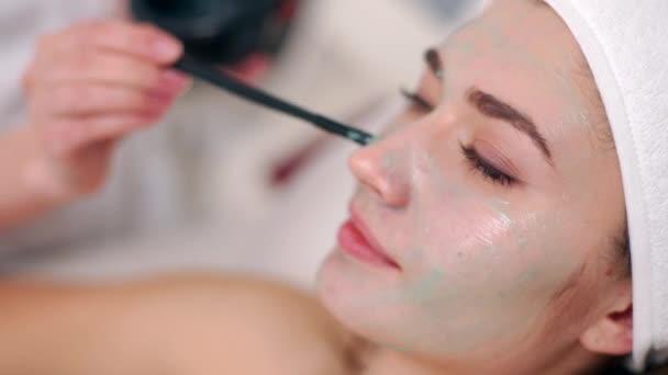 Kozmetológiai szakember alkalmazása arcpakolás ecsettel, hogy a bőr hidratált és egészséges. Vonzó nő pihentető csukott szemmel, és élvezi bőrápoló Spa eljárásokat. Kozmetikus munka.