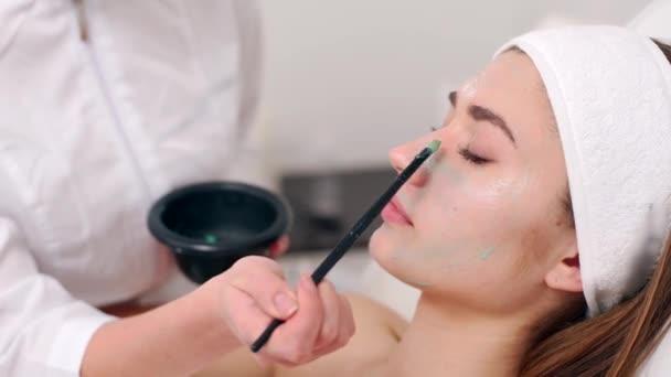 Specialista kosmetologie aplikoval masku obličeje štětcem, čímž se pokožka hydratuje a zdraví. Přitažlivá žena s zavřenýma očima a užívající si lázeňské procedury. Beauticijník v práci.