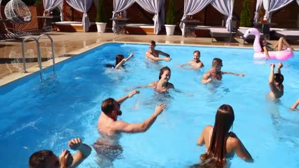 Friends have party in a private villa swimming pool. Happy young people in swimwear splashing water, dancing with floaties and inflatable mattress in luxury resort on sunny day. Slow motion.