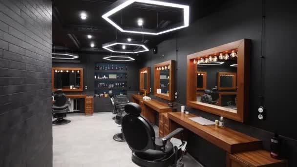 Tradiční interiér holičství - pohyb po židlích, dřevěných stolech a zrcadlech. Stylové kadeřnické studio uvnitř. Stylový design salonu krásy s moderním osvětlením a lampami.
