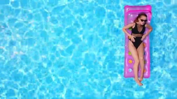 Csinos lány bikiniben, felfújható rózsaszín matracon, úszómedencében. Fürdőruhás, barna ruhás nő. Női pihenés a lebegő kék víz luxus üdülőhely. Légi, felülnézetből.