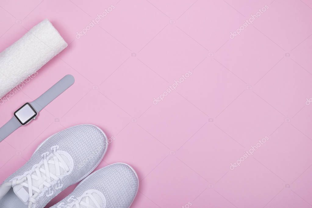 White sport shoes (sneakers) with smart watch (activity tracker) and towel on pink color background.