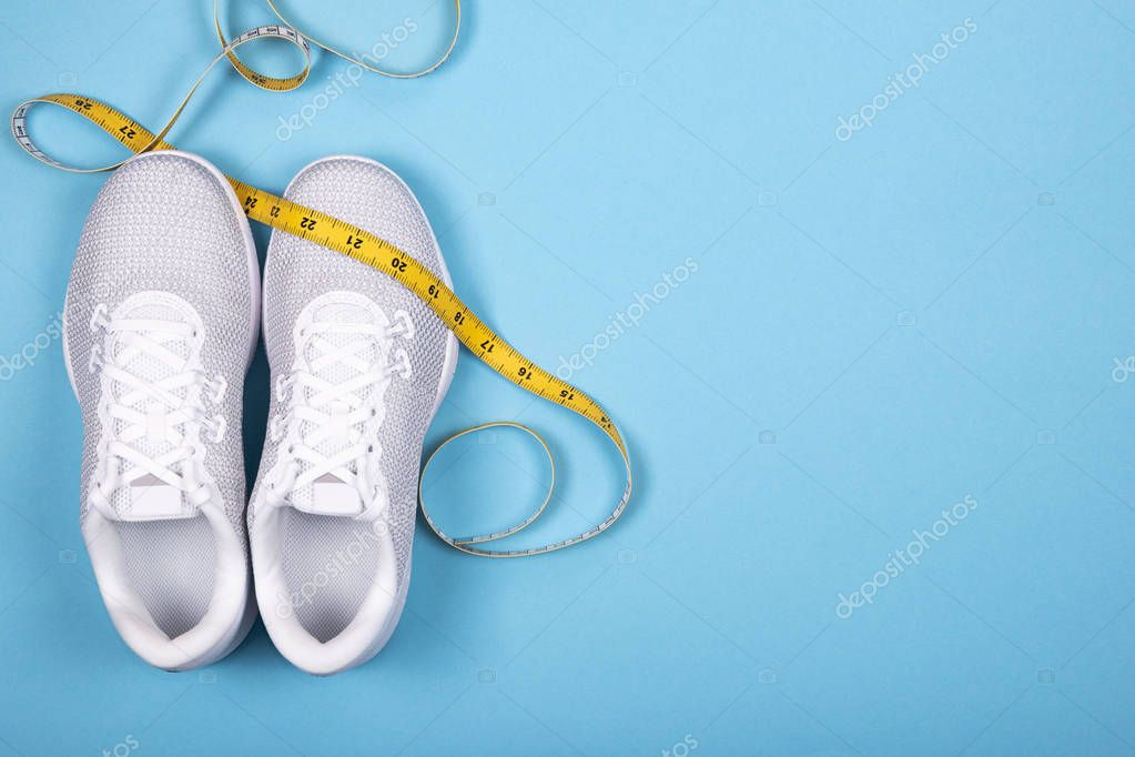 White sport shoes (sneakers) with measuring tape on blue background.