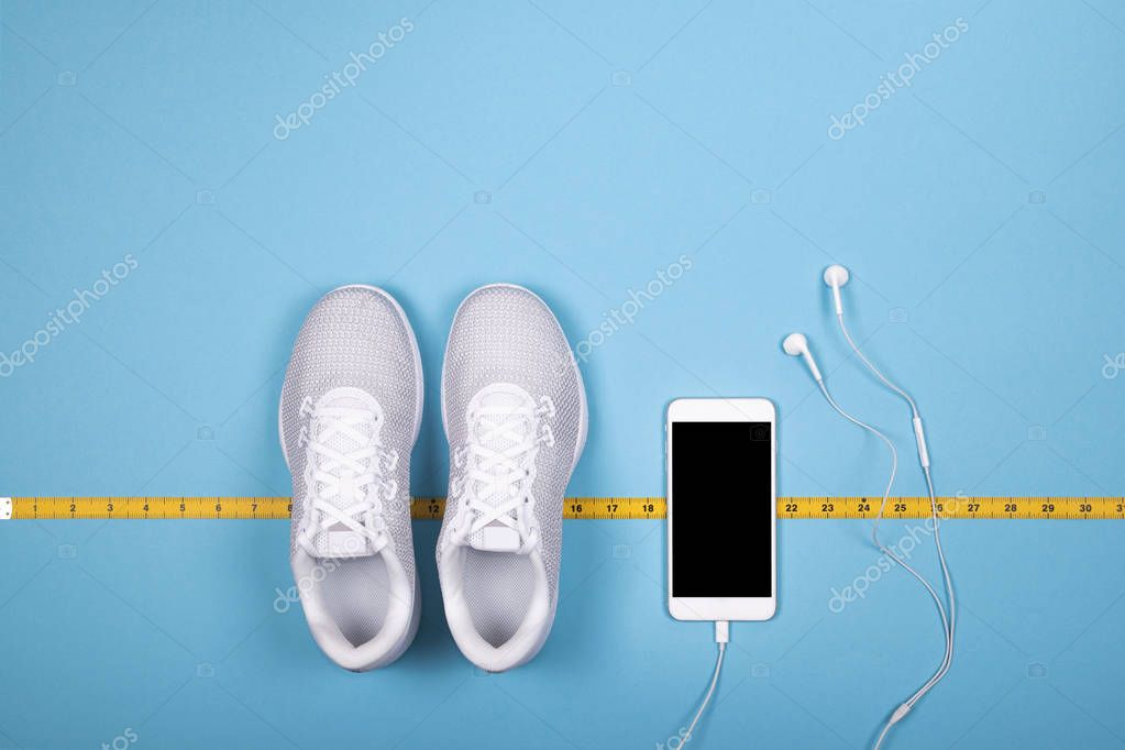 White sport shoes (sneakers) with measuring tape decimeter, smart phone and white earphones (headphones) on blue background.