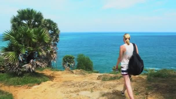 girl tourist travels in Asia, comes with a backpack on a tropical forest with palm trees and sea views