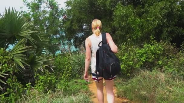 tourist woman with a backpack walking on a tropical forest on the island