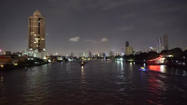View of skyscrapers on skyline from river and boats traffic at night