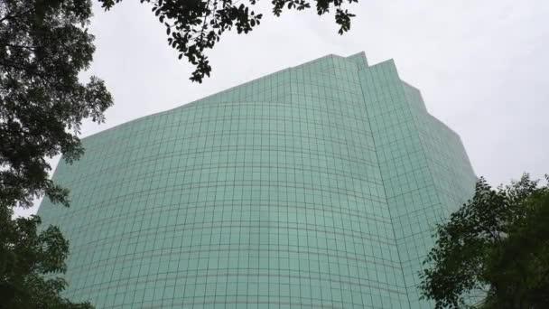 Glassy windows of modern hightech building across the green tree at daylight