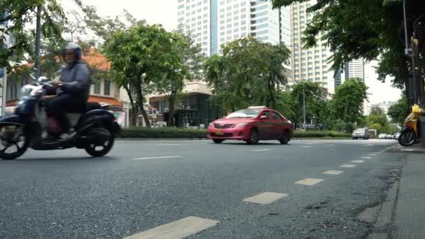 Vozovky v centru města s motocykly a automobily, kancelářské budovy v pozadí