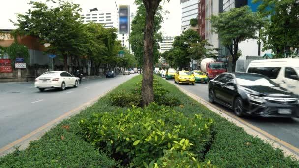 Provoz na rušné avenue v letní den, zelená ulice v centru města Bangkok