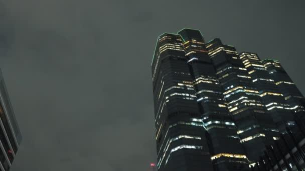 Vrchol věže budovy v centru města, v noci osvětlenými mrakodrapy na pozadí oblohy