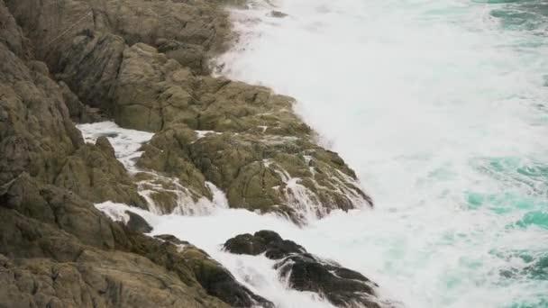 Hullámok ostromolják sziklák az óceánban, fröccsenő tengeri hab