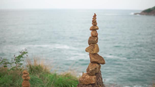 Zen Stones stacked at the top of green hill. The concept of harmony and balance
