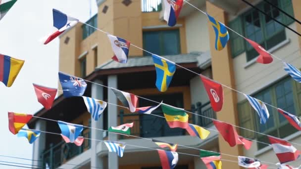 Multi-colored flags of many countries are waving in the air, slow motion. Unification of different states concept