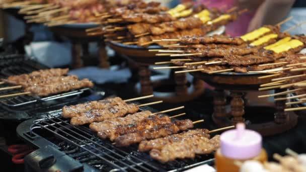 Pomalý pohyb, příprava malých lahodných kebabů na rozpáleném grilu. Tradiční trh potravinářských ulic v Thajsku