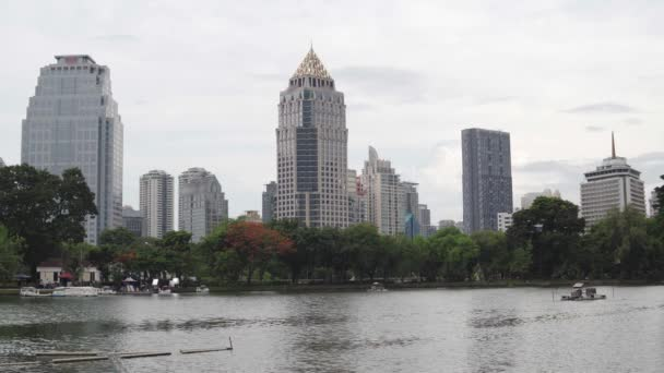 Calm cityscape at the daytime in summer. Ripples on the water on the city lake surface. Modern high-rise buildings over the green Park