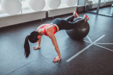 Anonymous woman doing plank on ball