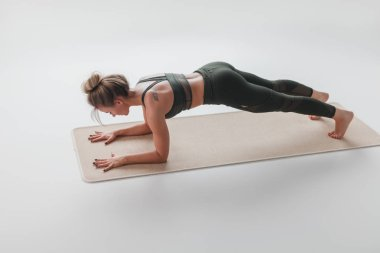 Woman in plank position on mat