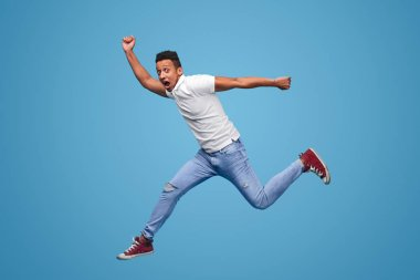 Side view of young African hipster in casual outfit screaming and looking at camera while jumping against blue background stock vector
