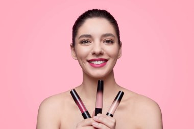 Smiling female with set of lipsticks