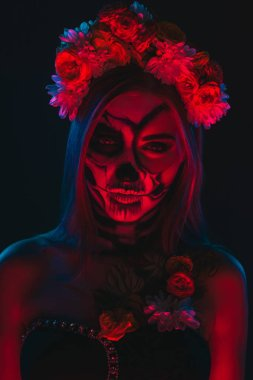 Spooky young female with skeleton makeup wearing floral wreath under bright and red illumination during Halloween party in dark room stock vector