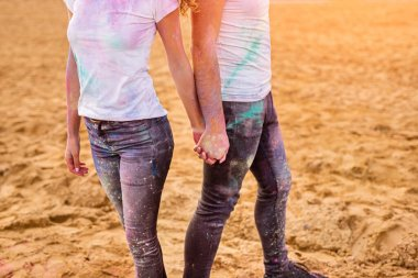 Crop couple holding hands during music festival